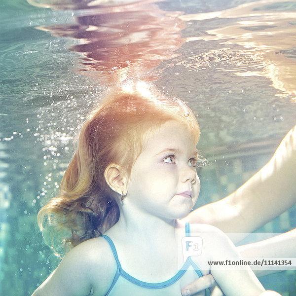 Caucasian girl swimming under water Caucasian girl swimming under water