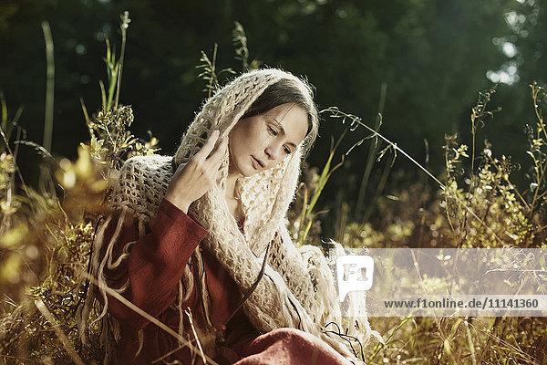 Caucasian woman in scarf sitting in field