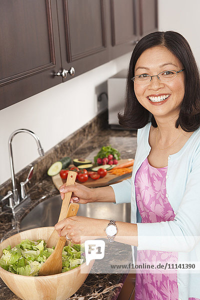 Chinese woman tossing salad in kitchen