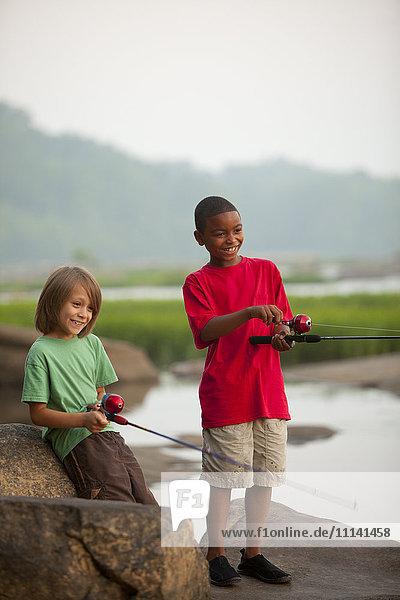 Smiling boys fishing together
