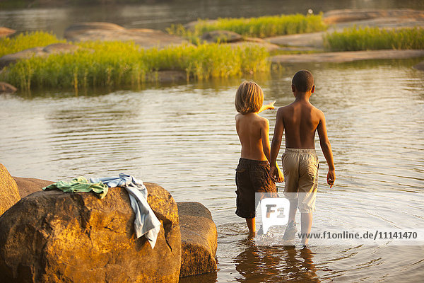 Boys wading in lake together