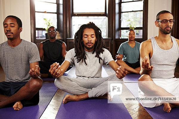 Men meditating in yoga class