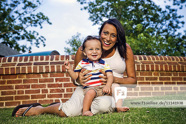 Mixed race mother and son sitting in grass