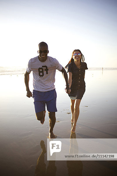 Happy couple holding hands and running on beach