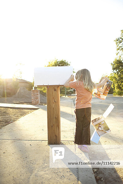 Caucasian man throwing mail out of mailbox