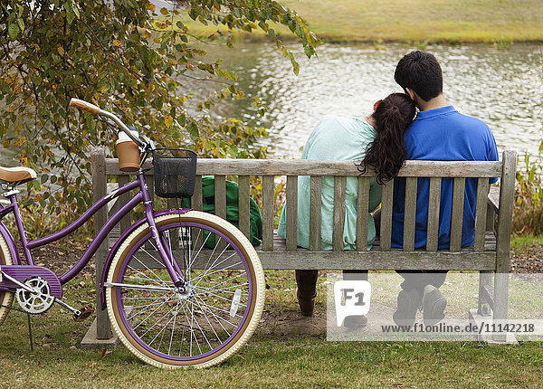 Student couple sitting on park bench