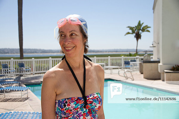 Caucasian woman in goggles and swim cap by swimming pool