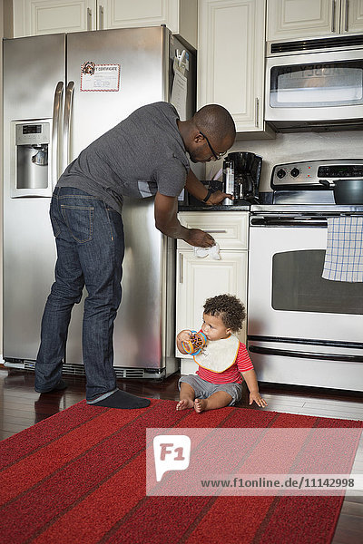 Father and toddler son in kitchen