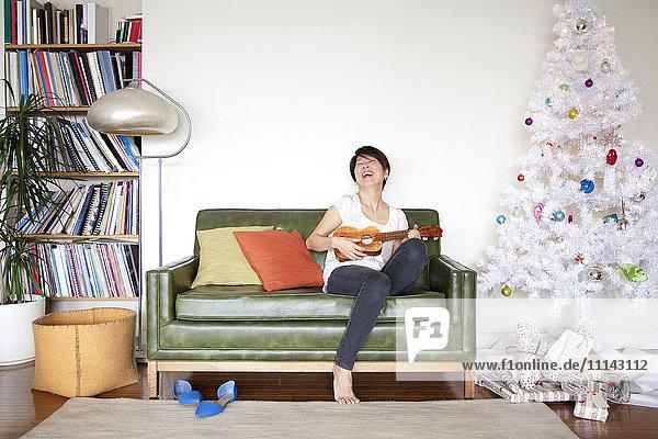 Japanese woman playing ukulele near Christmas tree