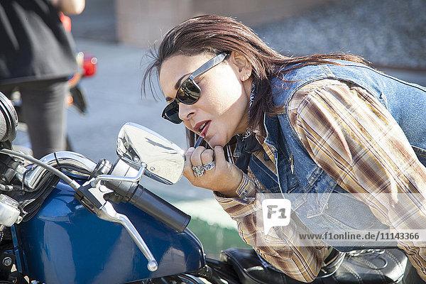 Woman applying makeup in motorcycle mirror
