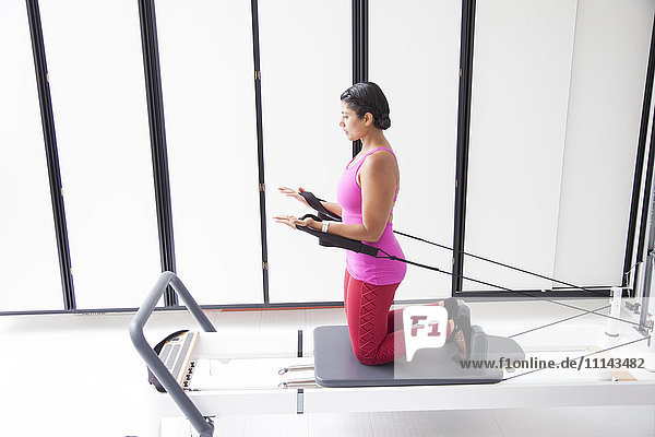 Asian woman using exercise machine in gymnasium