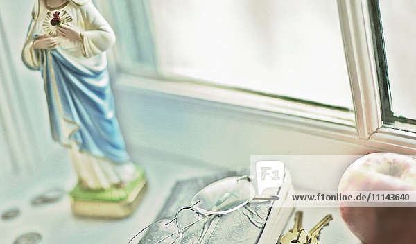 Close up of glasses  religious statue and fruit on windowsill