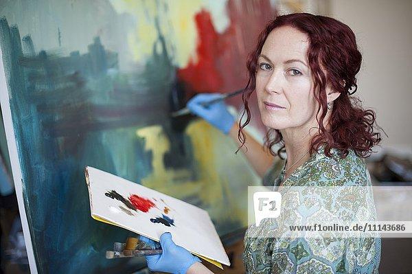 Artist painting on canvas in studio