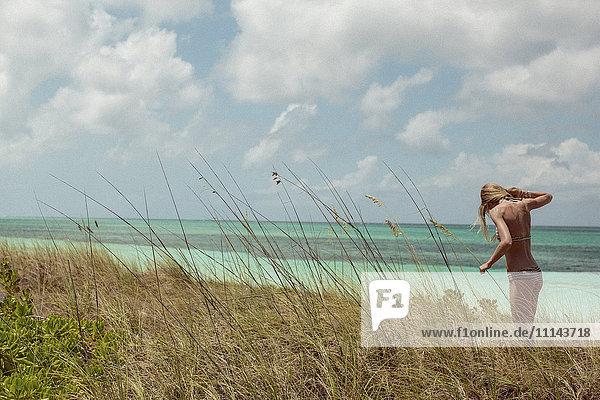 Woman in bikini standing in beach grass