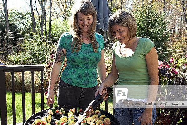 Women grilling kebabs in backyard