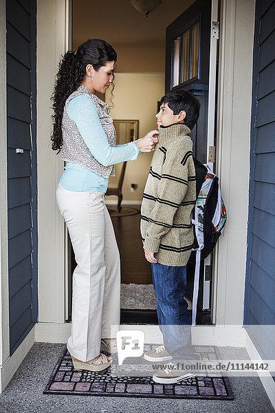 Hispanic mother zipping son's jacket at door