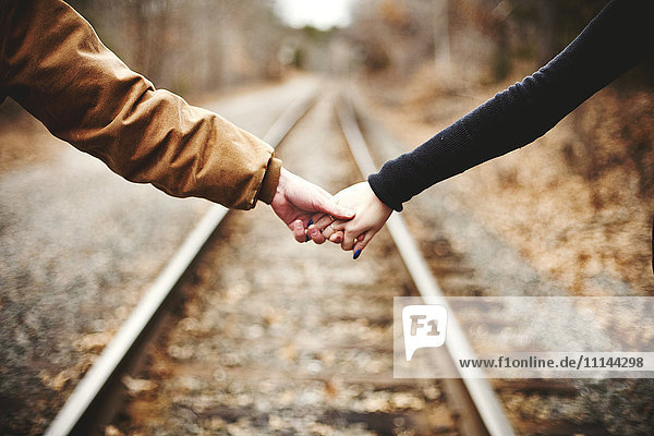 Close up of couple holding hands on railroad tracks