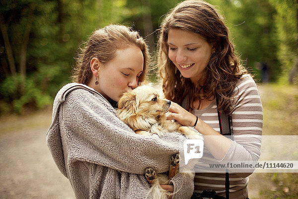 Girls petting puppy in forest