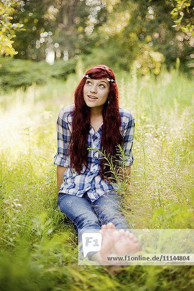 Girl wearing flower crown in rural field