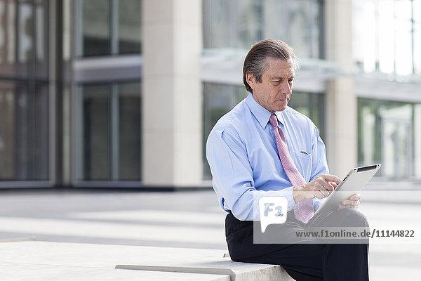 Caucasian businessman using digital tablet in courtyard