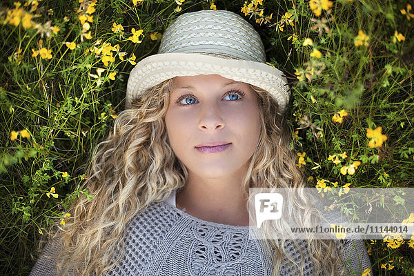 Woman in straw hat laying in flowers
