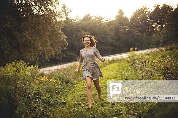 Smiling woman running in rural field
