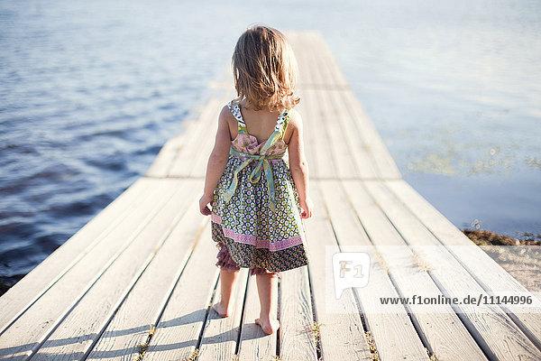 Girl walking on wooden dock over rural lake