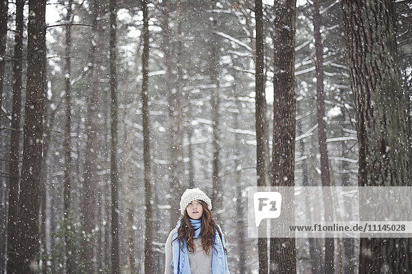 Girl standing in snowy forest