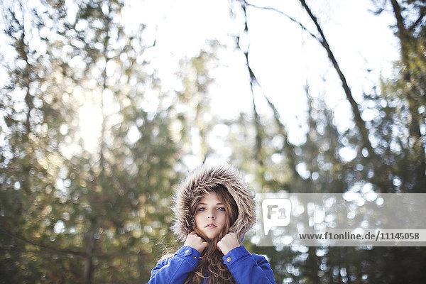 Woman wearing fur hood under trees Woman wearing fur hood under trees