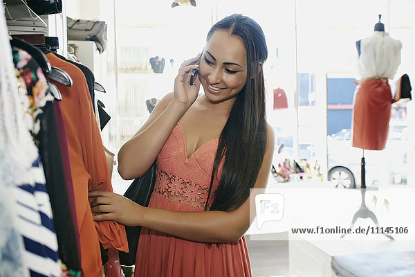 Mixed race woman talking on cell phone and shopping in store