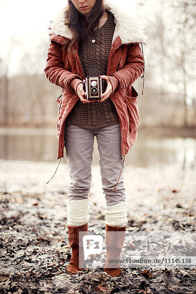 Caucasian woman photographing with vintage camera near rural pond