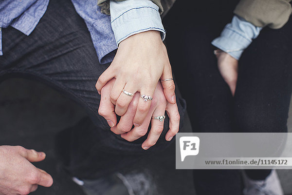 Close up of Caucasian couple holding hands