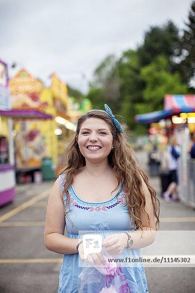 Caucasian woman eating candy at amusement park