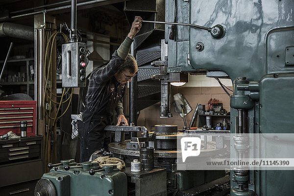 Caucasian man using machinery in metal shop