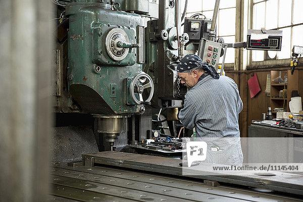 Man using machinery in metal shop