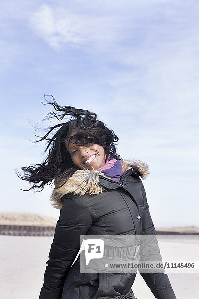 Woman in coat jumping for joy on beach