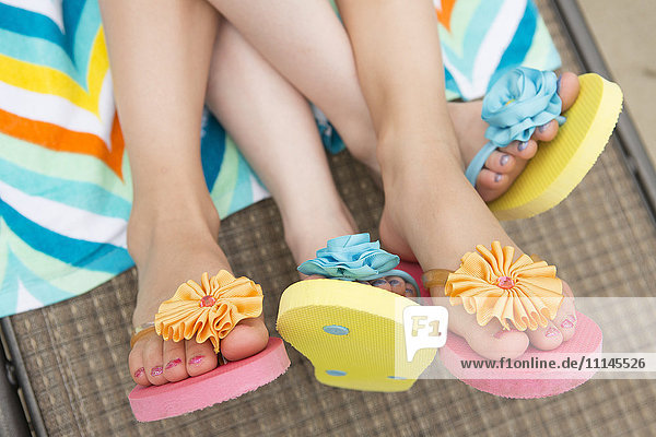 Close up of Caucasian girls wearing flipflops on lawn chair