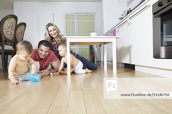 Caucasian family playing on kitchen floor