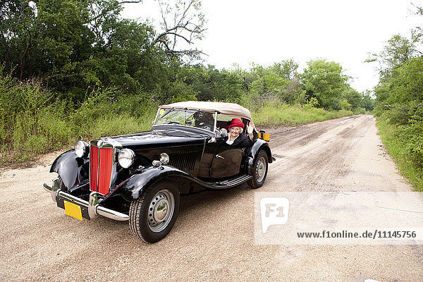 Older Caucasian woman driving convertible on rural road