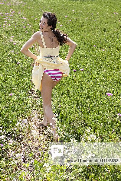Caucasian woman flashing her underwear in field