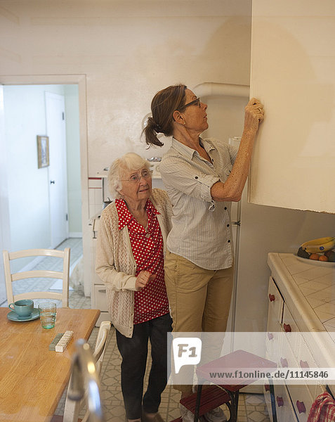 Caregiver reaching in cabinet for older woman