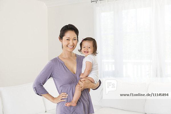 Mother holding baby girl in living room
