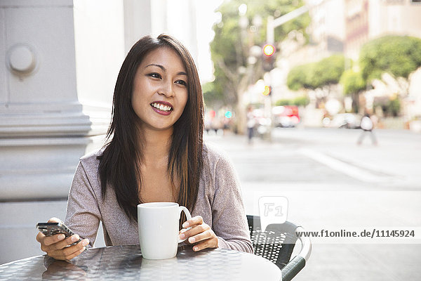 Woman with cell phone enjoying coffee at sidewalk cafe