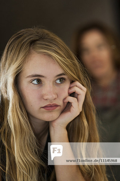Serious teenage girl examining herself in mirror