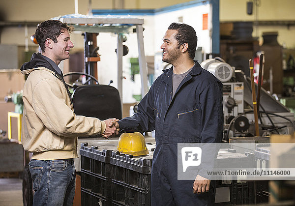 Workers shaking hands in warehouse