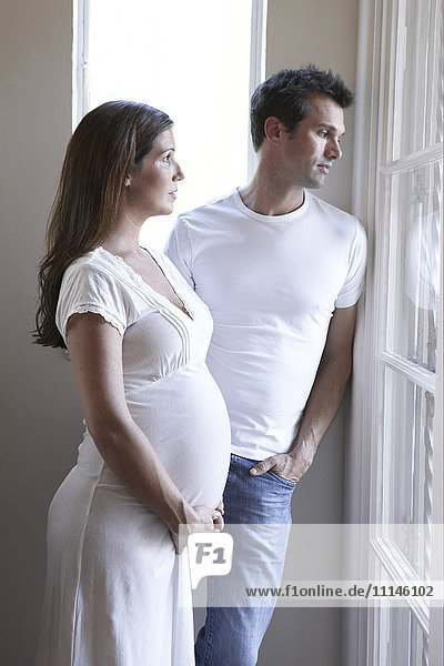 Serious pregnant couple looking out window