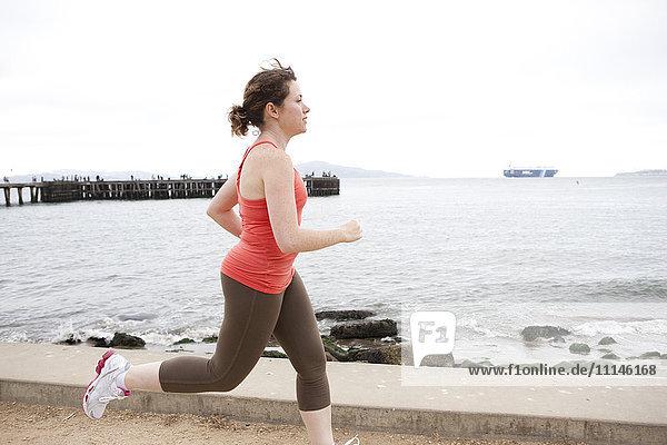 Caucasian woman running on waterfront