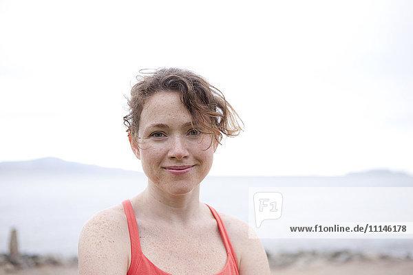 Caucasian woman smiling on rocky beach