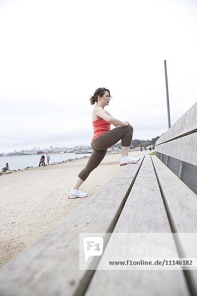 Caucasian woman stretching on beach bench