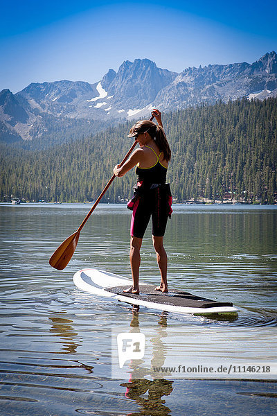 Mixed race woman on paddle board in Lake Tahoe  California  United States